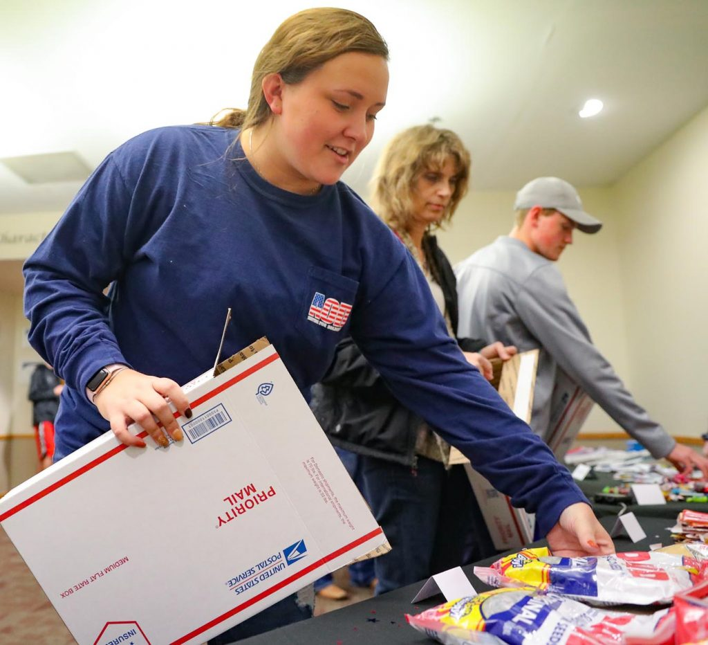 Alpha Omicron Pi's Ellie Stallbaumer of Cozad prepares a care package for Sisters for Soldiers, which sends items to service men and women spending the holidays away from their families. (Photo by Corbey R. Dorsey, UNK Communications)