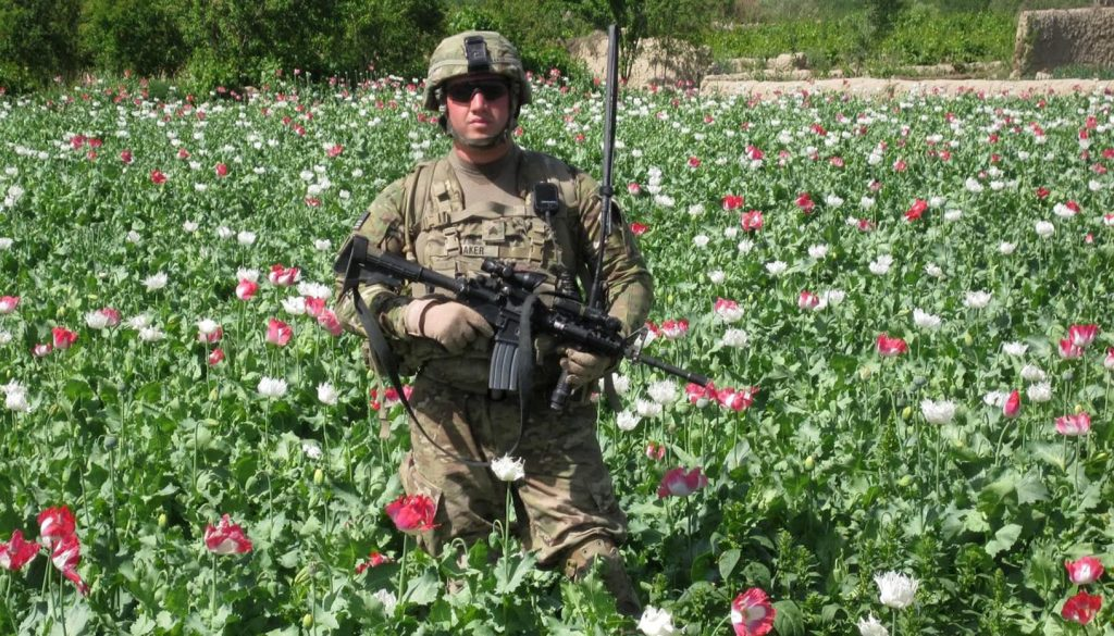 UNK student Jason Baker stands in a poppy field in Afghanistan, where he spent a year following a 2010 deployment with the U.S. Army. Farmers were pressured by the Taliban to grow the crop for heroin production. (Courtesy photo)