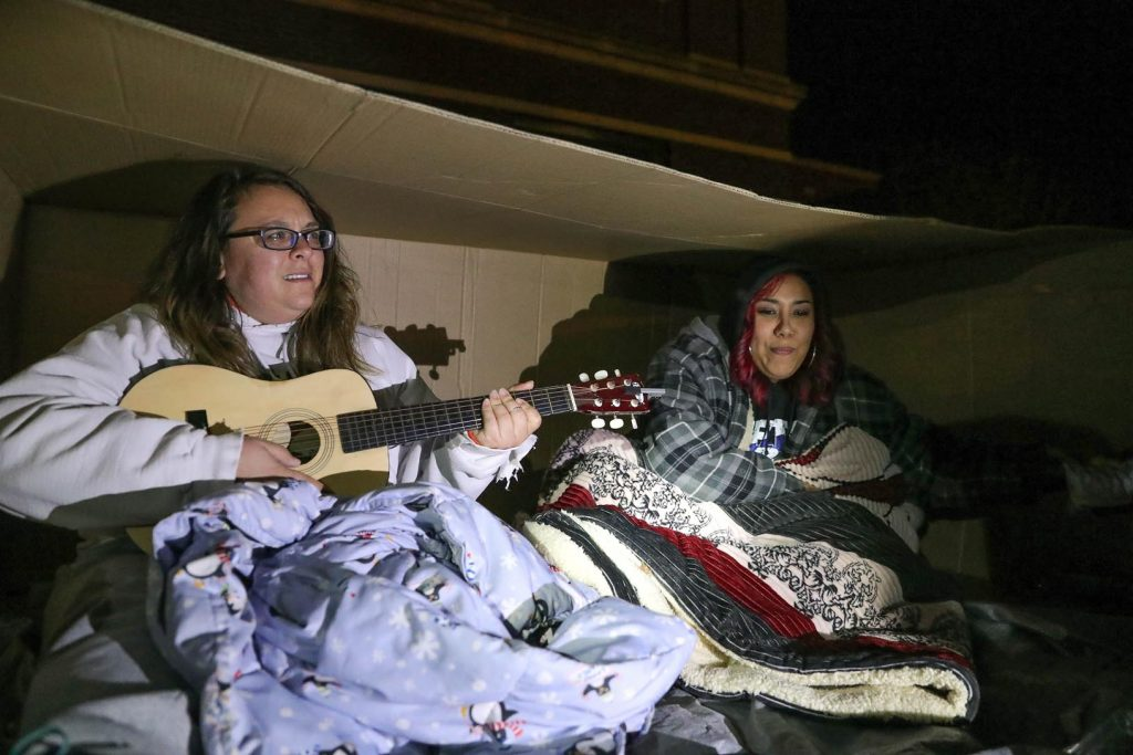 """UNK students, from left to right, Sadie Brandt, Carrie Hardage and Jayme Gomez, all of Kearney, slept outside in cardboard boxes Friday as part of Chi Sigma Iota's """"A Night Without a Home,"""" which raises awareness about homelessness. (Photo by Corbey R. Dorsey, UNK Communications)"""