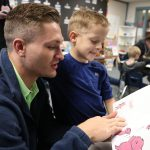 UNK wrestler Mike Lambert, a senior from Fremont, reads to Meadowlark Elementary School first-grader Barrett Hill during a recent visit. Members of the UNK wrestling team stop by the Kearney elementary school each week to read with students and participate in other fun activities. (Photo by Corbey R. Dorsey, UNK Communications)
