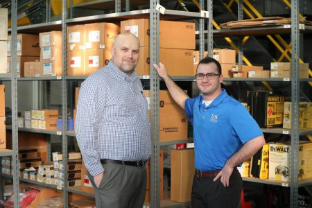 UNK industrial distribution students gain real-world skills while working inside a branch simulation lab filled with products donated by various companies. Program coordinator and lecturer Ben Brachle, left, is pictured with Levi Rosenquist, an industrial distribution major from Dannebrog. (Photo by Corbey R. Dorsey, UNK Communications)