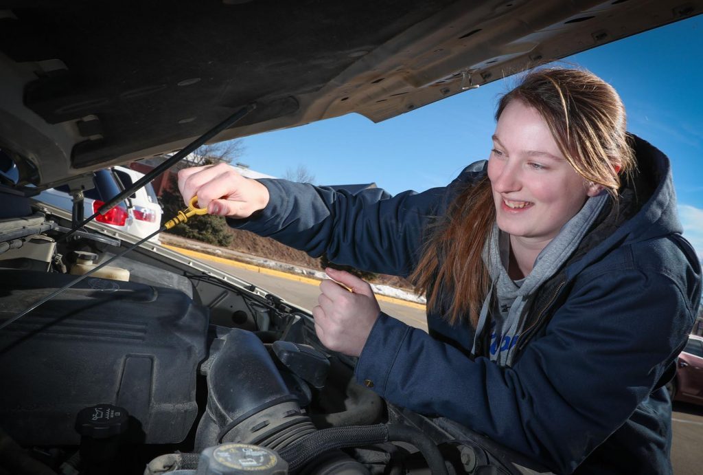 Freshman Brooke Carlson is the unofficial mechanic for the UNK women's basketball team. She's not afraid to get under the hood and get her hands dirty. (Photo by Corbey R. Dorsey, UNK Communications)