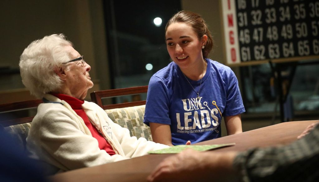 Kaitlyn Pineda, a UNK sophomore from Kearney, visits with Ellamae Moseley, a resident at the Central Nebraska Veterans Home in Kearney. Pineda and other members of the UNK Leads program stopped by the veterans home Wednesday evening to tour the facility and play bingo with residents. (Photo by Corbey R. Dorsey, UNK Communications)