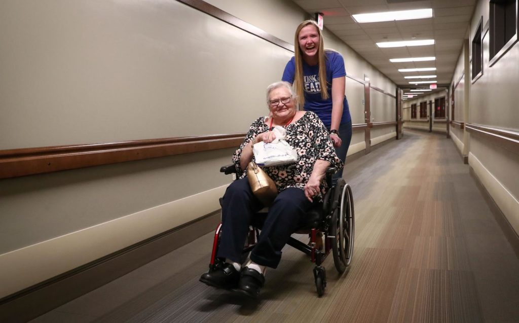 UNK student Lydia Behnk of Elgin and Central Nebraska Veterans Home resident Geri Ward head to the bingo room Wednesday evening for a little fun. Members of the UNK Leads program toured the veterans home in Kearney before playing bingo with residents. (Photo by Corbey R. Dorsey, UNK Communications)
