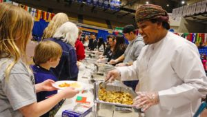 Jahad Al Bulushi, a UNK student from Oman, serves chicken kabuli to a line of hungry attendees at Sunday's Scott D. Morris International Food and Cultural Festival. Dishes from nine countries were featured during the annual event at UNK's Health and Sports Center. (Photo by Todd Gottula, UNK Communications)