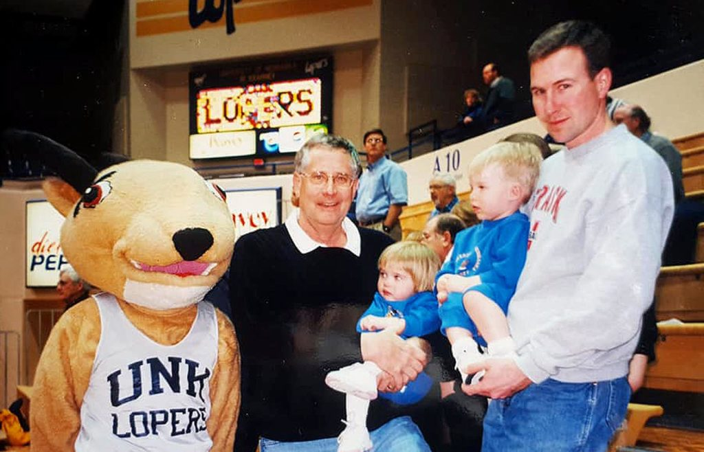 A very young Morgan and Trevor Daubert attend a UNK basketball game in 2001 with their father Mike, right, grandfather Les Livingston and a very old Louie the Loper mascot. (Courtesy photo)