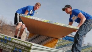 UNK students Zach Ciborn of Columbus, left, and Riley Mrkvicka of Farwell load Sheetrock off a semitrailer Saturday while helping with flood recovery efforts in Gibbon. They joined 500 other University of Nebraska at Kearney students who volunteered in Kearney and area communities as part of UNK's The Big Event. (Photo by Corbey R. Dorsey, UNK Communications)