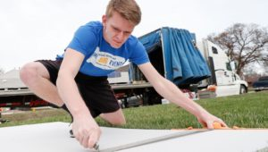 Connor Rockwell of Norfolk cuts Sheetrock Saturday while helping with flood recovery efforts in Gibbon. Rockwell was among 500 University of Nebraska at Kearney students volunteering in Kearney and area communities as part of UNK's The Big Event. (Photo by Corbey R. Dorsey, UNK Communications)
