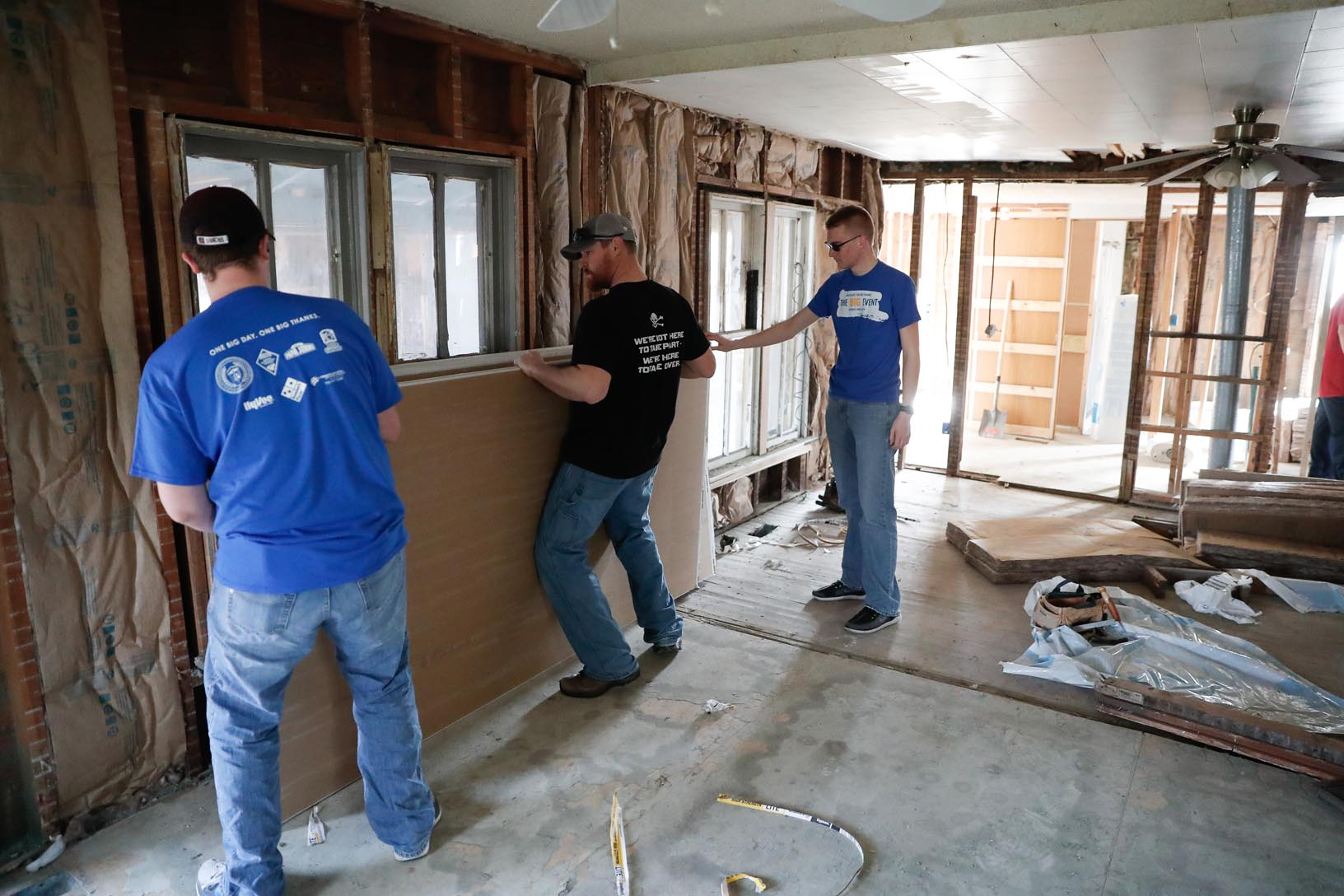 UNK students Jaden Powers of Central City, left, and Jacob Nutter of Geneva, right, put up drywall Saturday with Trevor Clark of Kearney inside a Gibbon home damaged by floods. The work was part of The Big Event, which included 500 UNK students who volunteered in Kearney and surrounding communities. (Photo by Corbey R. Dorsey, UNK Communications)