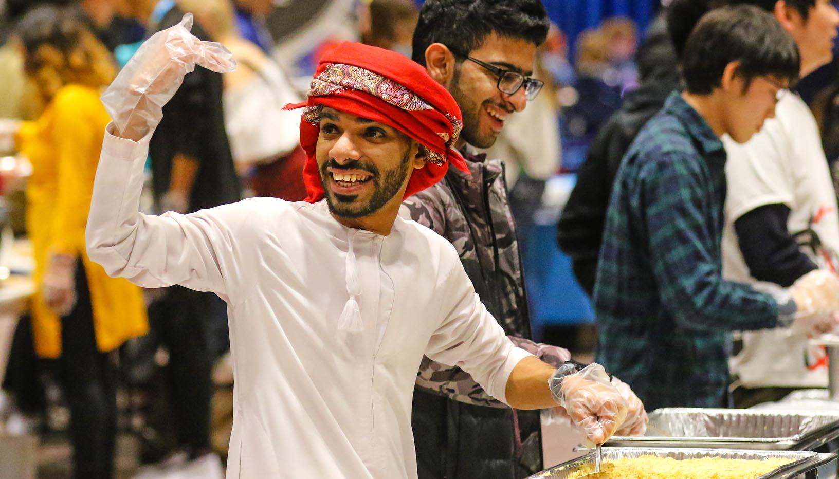 Khalid Alrasbi of Oman serves food at UNK's International Food and Cultural Festival. (Photo by Todd Gottula, UNK Communications)