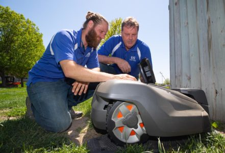 Michael Sup, left, and Dick Wardyn with UNK Facilities Management and Planning set up a robotic mower at its charging station on campus. UNK owns two Husqvarna Automowers that maintain the marching band practice field between the College of Education building and West Center. (Photo by Corbey R. Dorsey, UNK Communications)