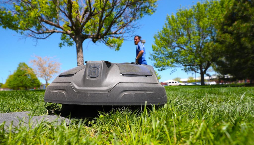 A robotic mower cuts grass at the marching band practice field between the College of Education building and West Center on the UNK campus. UNK purchased two of the machines for a pilot project aimed at increasing efficiency and reducing expenses within the facilities management department. (Photo by Corbey R. Dorsey, UNK Communications)