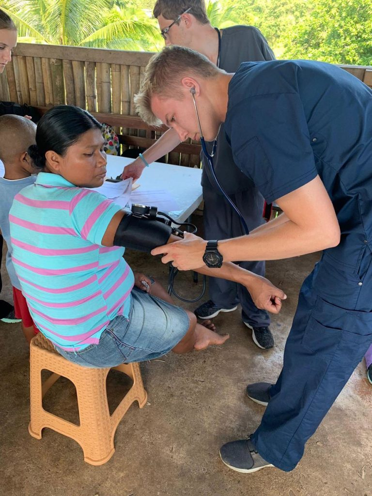 UNK student Trevor Daubert checks a patient's vital signs at a mobile medical clinic in Panama. Twenty-one members of the UNK chapter of Volunteers Around the World traveled to the Central American country last month to work in mobile medical clinics that provided free care and medication to more than 300 patients. (Courtesy photo)