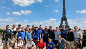 Members of the UNK wrestling program pose for a photo near the Eiffel Tower while visiting Paris, France. Loper wrestlers, coaches and alumni spent a day in Paris before flying to Athens, Greece, during last month's international trip. (Courtesy photo)