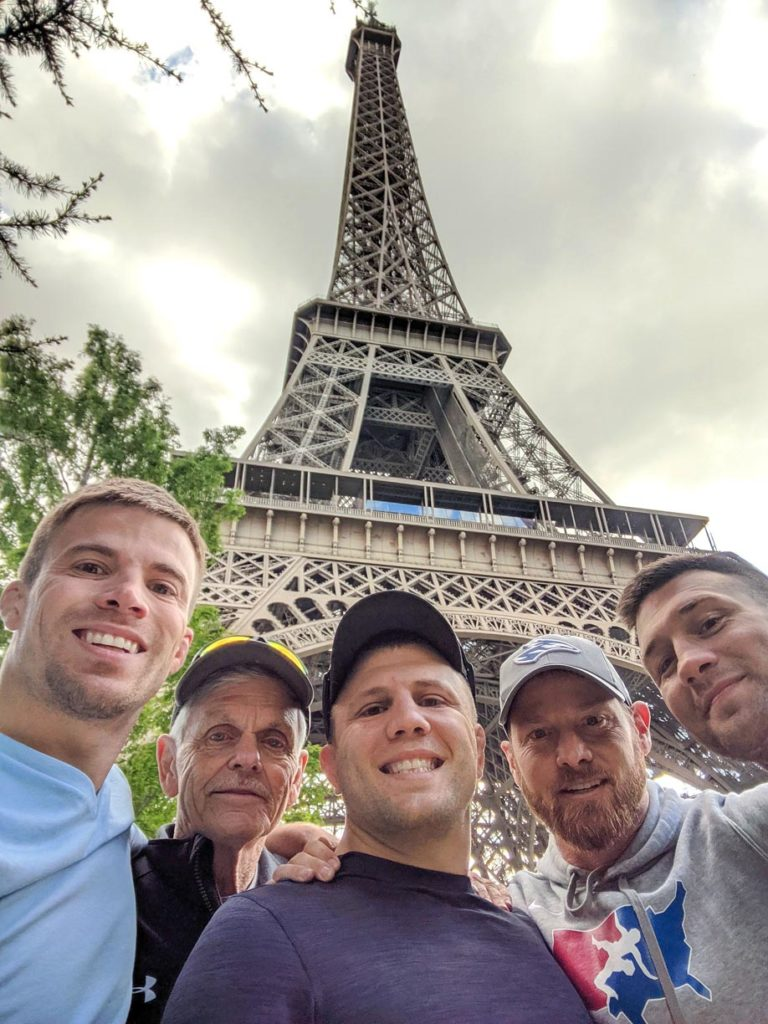 From left, UNK head wrestling coach Dalton Jensen, UNK assistant coach Tom McCann, Loras College assistant coach Trevor Kittleson, UNK alumnus Kurt Karjalainen and UNK assistant coach Andrew Sorenson snap a selfie with the Eiffel Tower in the background while visiting Paris, France, during last month's international trip. (Courtesy photo)