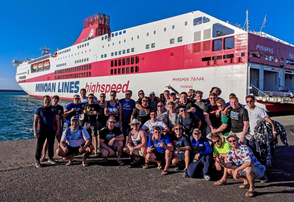 UNK wrestlers, coaches and alumni take a photo near the ferry that transported them from Athens, Greece, to Crete during last month's international trip. (Courtesy photo)