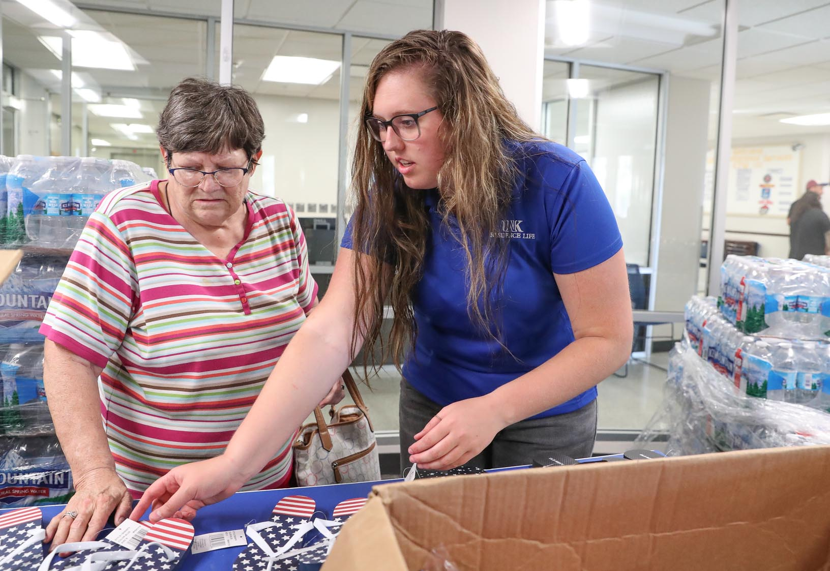 Stacea Pauli with UNK's Office of Residence Life, right, assists a woman impacted by Tuesday's flooding in the Kearney area. UNK opened two residence halls to provide housing for flood evacuees. (Photo by Corbey R. Dorsey, UNK Communications)