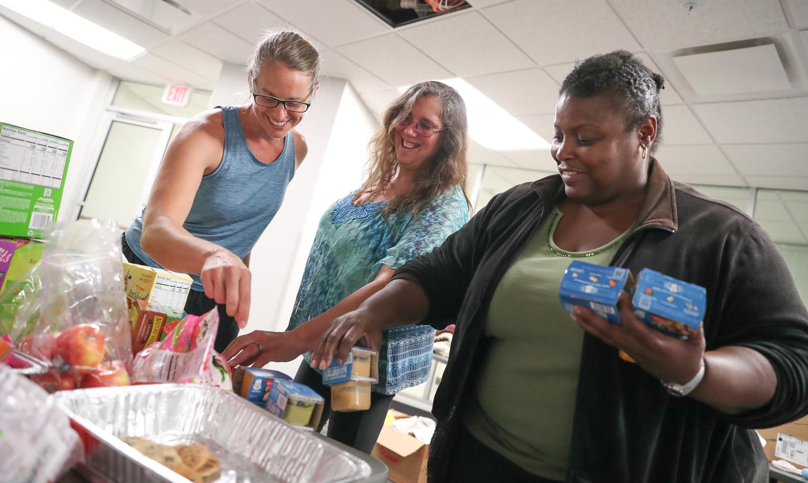 From left, Jennifer Bennetts of Lincoln, Sue Lasek of Milford and Geri Anderson of Omaha drop off food and supplies for flood evacuees Tuesday at UNK's Centennial Tower West residence hall. UNK opened two residence halls to provide housing for people impacted by flooding. (Photo by Corbey R. Dorsey, UNK Communications)