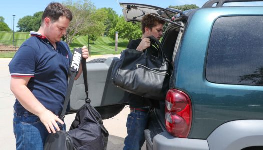 Logan Jeffers, left, of Omaha and Tyler Tracy of Kearney load up their belongings Friday awhile moving out of UNK's Centennial Towers West residence hall. The two were among more than 330 people who occupied rooms at UNK and received meals after flooding hit the city. (Photo by Corbey R. Dorsey, UNK Communications)