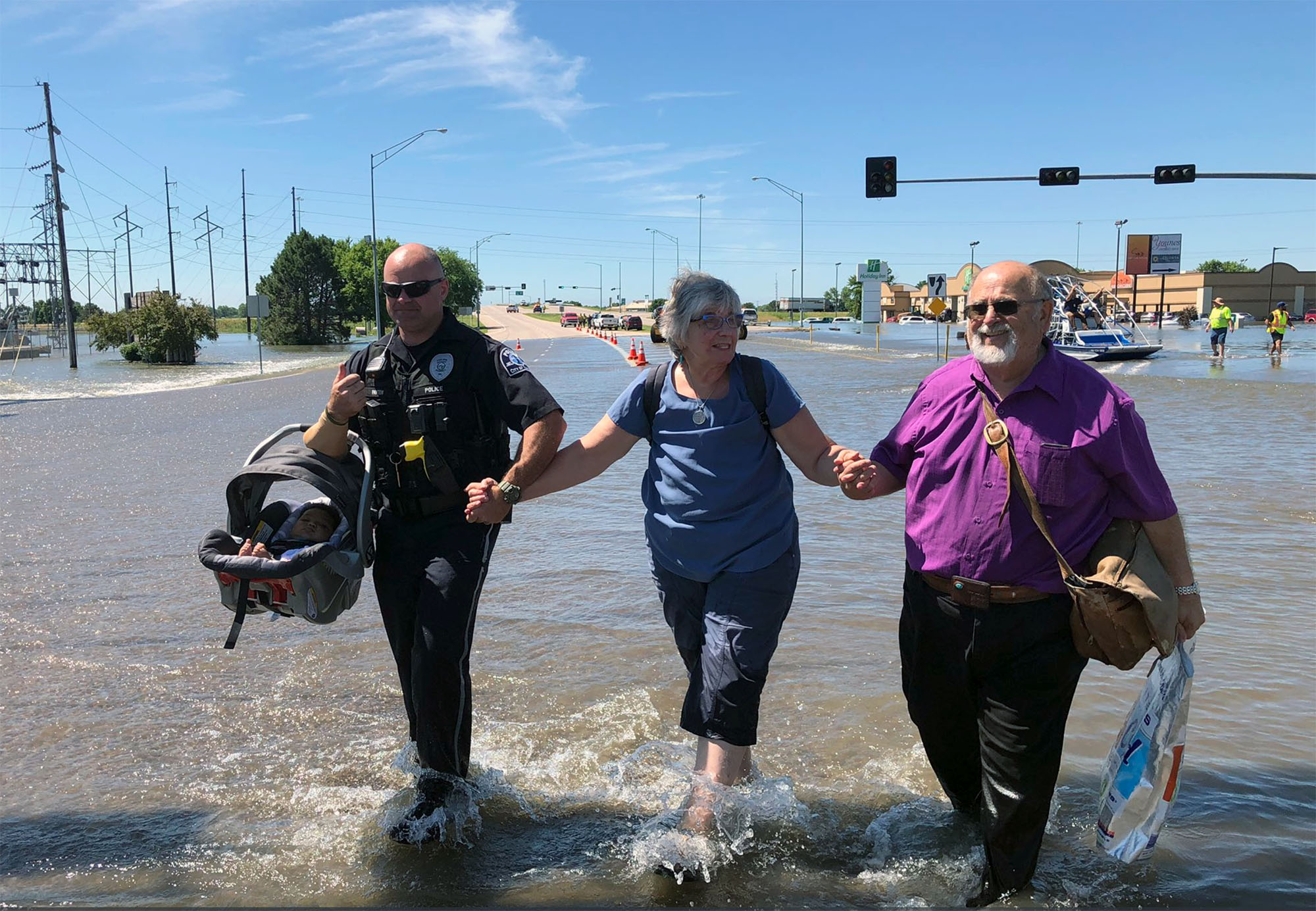 Kearney Police Officer Derek Payton assists Leslye and Terry Taylor of Pueblo, Colorado, and their 3-month-old grandson as they walk through the floodwater Tuesday after evacuating a local hotel. (Photo courtesy of Kearney Police Department)
