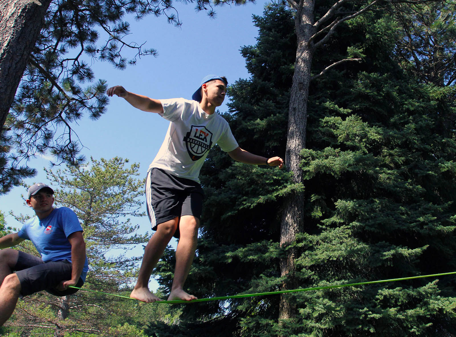 Isaac McDowell of Lexington tests his balance on a slackline while UNK senior Connor Gosnell provides some coaching. Incoming UNK freshmen participated in a variety of team-building activities at the Nebraska National Forest near Halsey during the First Adventure summer camp. (Photo by Tyler Ellyson, UNK Communications)