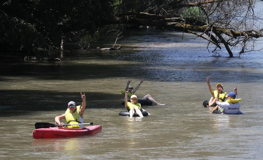 """UNK students """"throw the lopes"""" while floating down the Middle Loup River near Halsey. Incoming freshmen spent time at the Nebraska National Forest this week during the First Adventure summer camp. (Photo by Tyler Ellyson, UNK Communications)"""