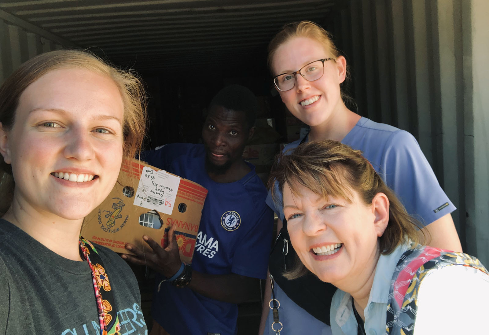 Tessa Copp, Michaela Walker and Michelle Fleig-Palmer pause for a photo while distributing donations during their trip to Zambia. (Courtesy photo)
