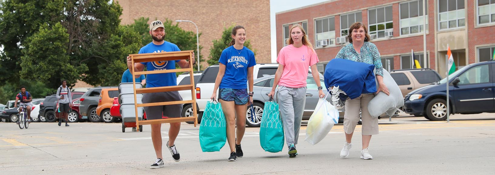 """From left, UNK students Alex Duncan of Gering and Nicole Kent of Benkelman help Sydney Kerr of Hastings and her mother Stacy on Wednesday as Kerr moves into Men's Hall on the UNK campus. Upper-level students from the Kearney Health Opportunities Program (KHOP) volunteered to assist new members with the move-in process. """"This helps us meet some of the new students and make sure they feel welcome,"""" Duncan said. """"KHOP is a group effort. We want them to know they're part of a great team."""" (Photo by Corbey R. Dorsey, UNK Communications)"""