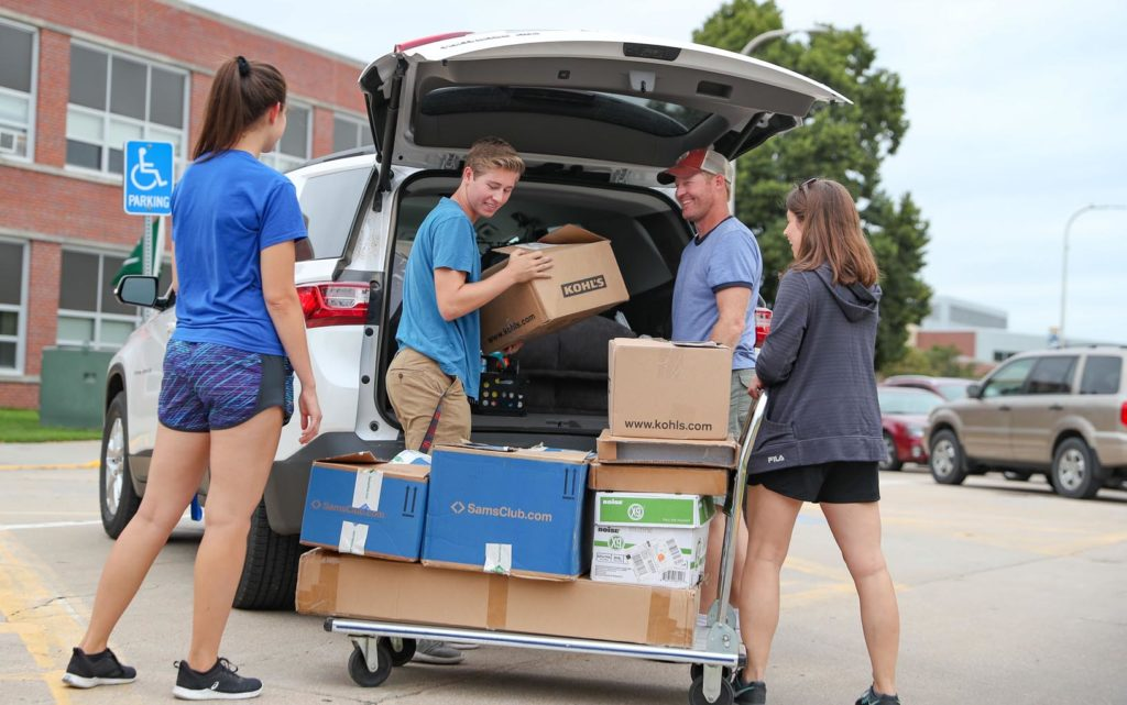 From left, UNK Student Body President Nicole Kent lends a hand Wednesday as Trenten Theis of Superior and his parents Nick and Julie unload boxes to move into a UNK residence hall. Theis and hundreds of other UNK students are moving into campus housing this week. (Photo by Corbey R. Dorsey, UNK Communications)
