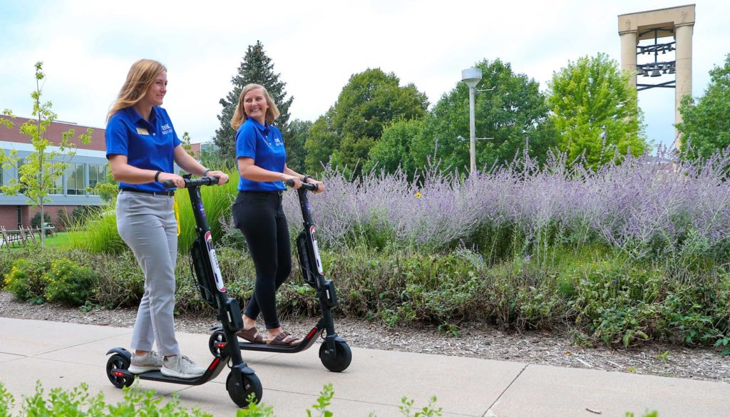 Students Rachel Higgins, left, and Courtni Heckert cruise around the UNK campus on electric scooters earlier this year. Nine scooters are available for students, staff, faculty and visitors to rent and ride at UNK. (Photos by Corbey R. Dorsey, UNK Communications)