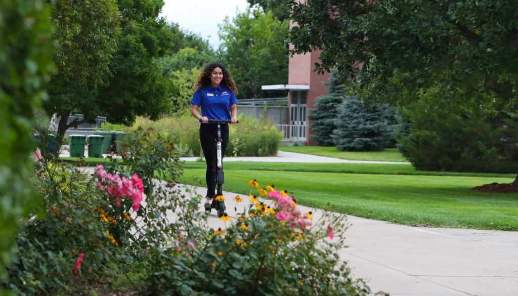 UNK student Catherine Arias Barrios rides one of nine electric scooters available for students, staff, faculty and visitors to rent and ride on campus.