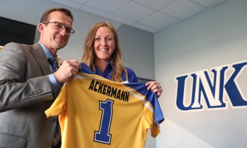 UNK Athletic Director Marc Bauer, left, presents a jersey to new Loper softball Head Coach Katie Ackermann at Wednesday night's news conference. (Photo by Corbey R. Dorsey, UNK Communications)