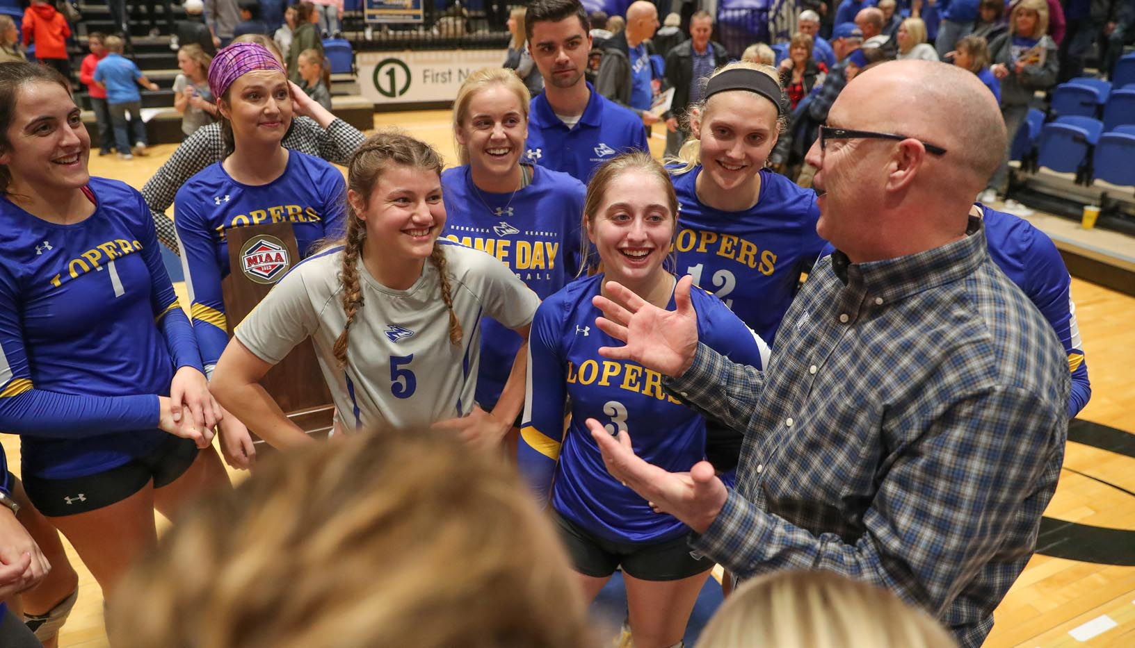 Inside UNK's Health and Sports Center, Rick Squiers focuses on his role as head coach of the Loper volleyball team, which includes his daughters Anna, left, and Maddie, back middle. Away from campus, he switches to dad mode. (Photo by Corbey R. Dorsey, UNK Communications)