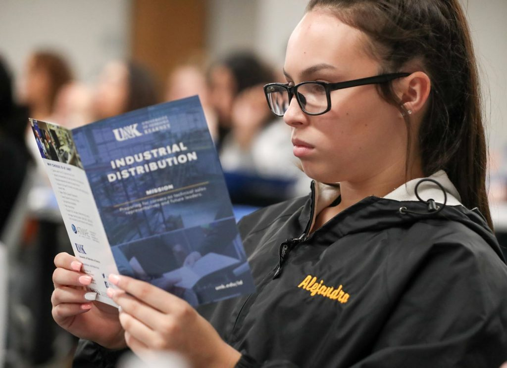 Fremont High School student Alejandra Pena reads a handout Tuesday while visiting the UNK campus. Pena and 44 other Fremont High students traveled to UNK to tour the campus and learn about the supply chain management and industrial distribution programs. (Photo by Corbey R. Dorsey, UNK Communications)