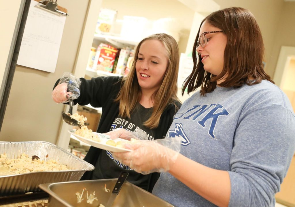 UNK students Shelby McDowell of Ogallala, left, and Alyssa Donahey of Palmer serve lunch to residents at the Crossroads Center homeless shelter Friday during a project for social work majors. (Photo by Corbey R. Dorsey, UNK Communications)