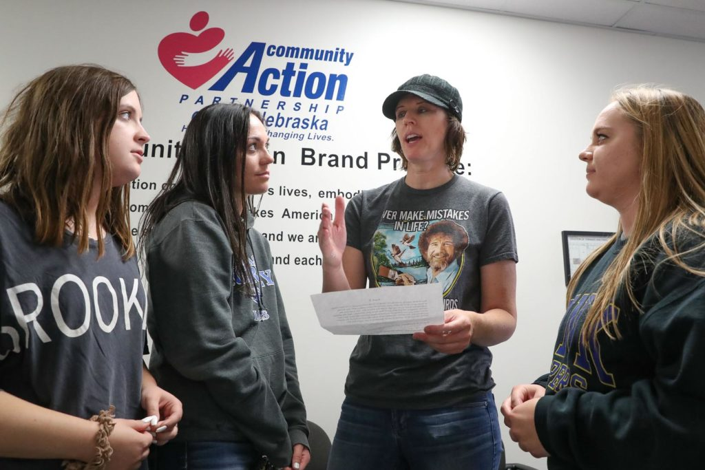 Community Action Partnership of Mid-Nebraska CEO Meredith Collins, second from right, shares information about the nonprofit organization with UNK students, from left, Sarah Tracy, Cassidy Eggers and Nina Wagoner. UNK social work majors visited various agencies Friday to learn more about local resources. (Photo by Corbey R. Dorsey, UNK Communications)