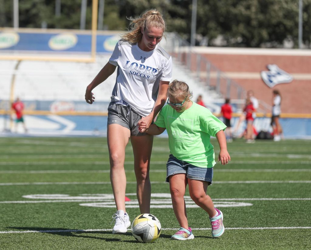 UNK soccer player Molly Willis walks a student through an activity at Cope Stadium during Early Awareness Day. Monday's event brought 73 area fourth graders to UNK to learn more about the university, explore potential careers and have a little fun. (Photo by Corbey R. Dorsey, UNK Communications)