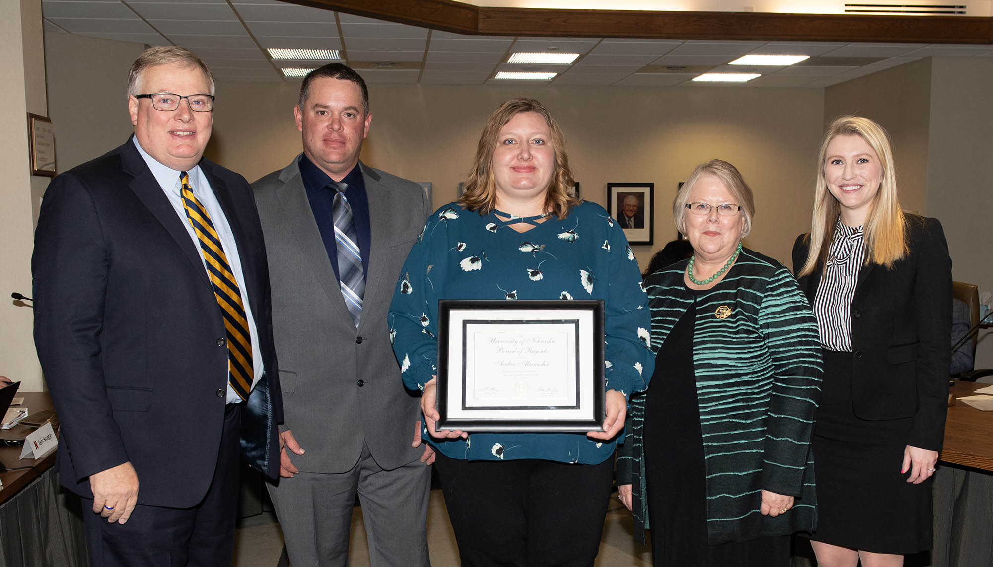 Amber Alexander, middle, was recognized with the KUDOS award at Friday's University of Nebraska Board of Regents meeting, which was attended by, from left, UNK Chancellor Doug Kristensen, Alexander's husband Nick, NU interim President Susan Fritz and Regent Elizabeth O'Connor. (Photo by Greg Nathan, NU Communications)