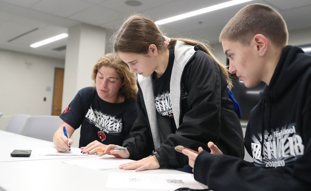From left, Scottsbluff High School students Talera Kinsey, Katherine Reisig and Leah Polk solve a math problem Friday during a scavenger hunt at UNK.