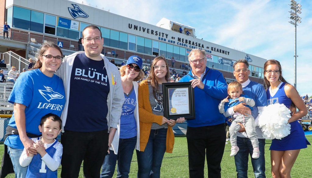 UNK Chancellor Doug Kristensen presents the Outstanding Family Award to Bill and Becky Williams of Kearney. Krista, far right, and Morganne, fifth from left, are current UNK students. Their oldest son Trevor and his wife Carly, far left, both graduated from UNK. (Photo by Corbey R. Dorsey, UNK Communications)