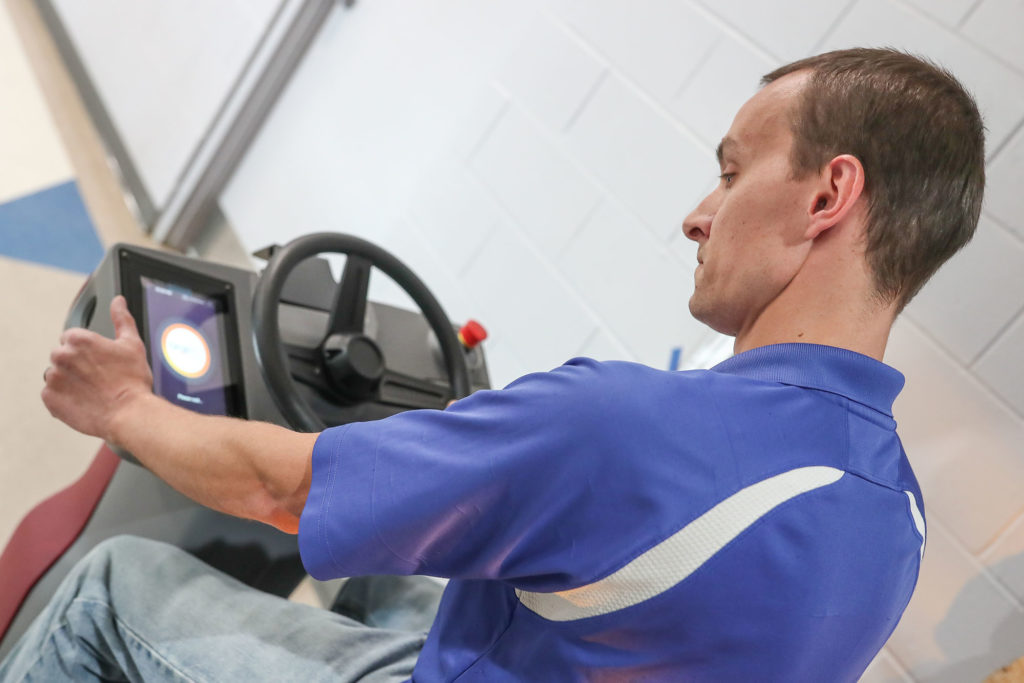 """Chris Blocher, lead custodian for UNK athletic facilities, starts a robotic scrubber that cleans the floors in the Health and Sports Center. """"It really makes a difference in terms of productivity and flexibility,"""" Blocher said of the autonomous machine introduced last month. (Photos by Corbey R. Dorsey, UNK Communications)"""