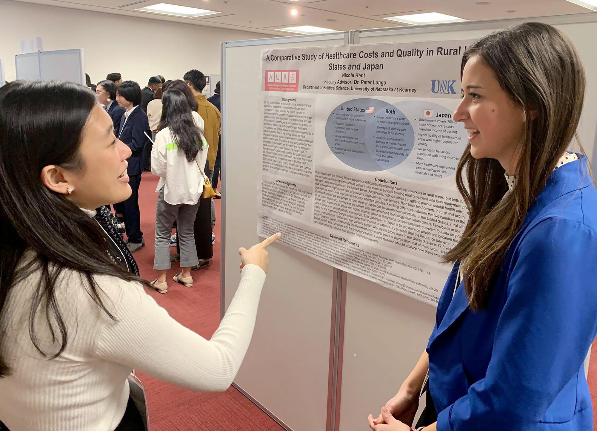UNK graduate Nicole Kent of Benkelman, right, discusses her study of health care costs and quality in the rural U.S. and Japan during the Asian Undergraduate Research Symposium in Tokyo.