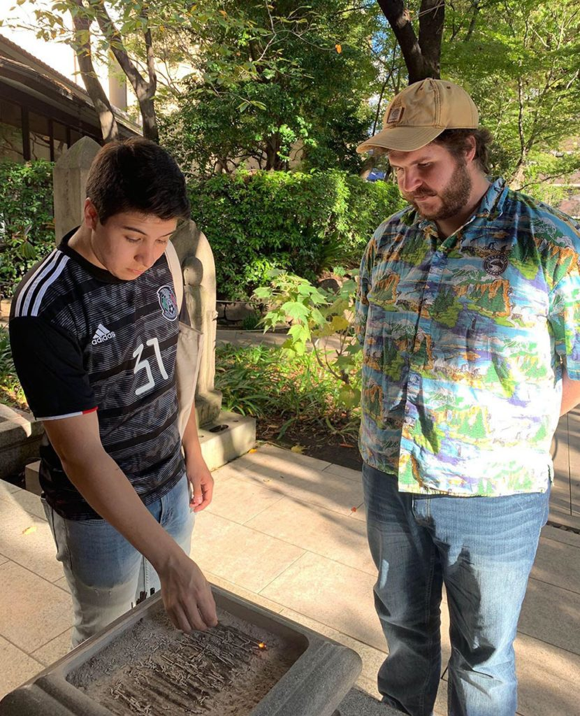 Adrian Gomez-Ramos, left, burns incense outside a temple in Tokyo while fellow UNK student Mic Rohde looks on.