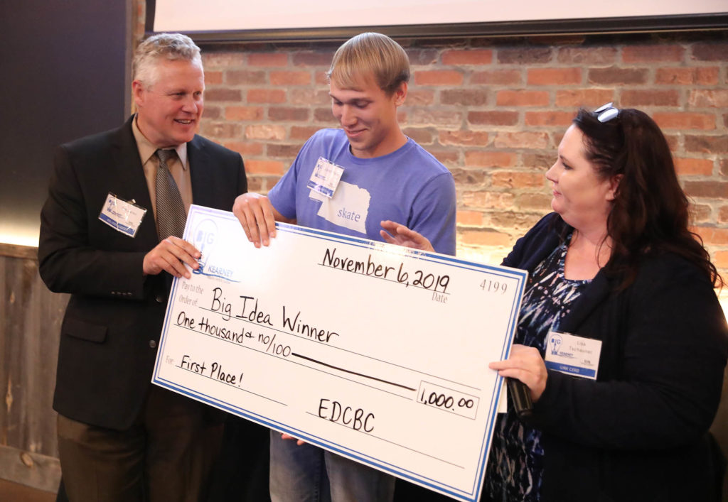 Jonah Staab of Kearney, center, receives a $1,000 check after winning the community division of the annual Big Idea Kearney competition. UNK College of Business and Technology Dean Tim Jares and Center for Entrepreneurship and Rural Development Director Lisa Tschauner presented the prize money during Wednesday night's event at Cunningham's on the Lake. (Photo by Corbey R. Dorsey, UNK Communications)