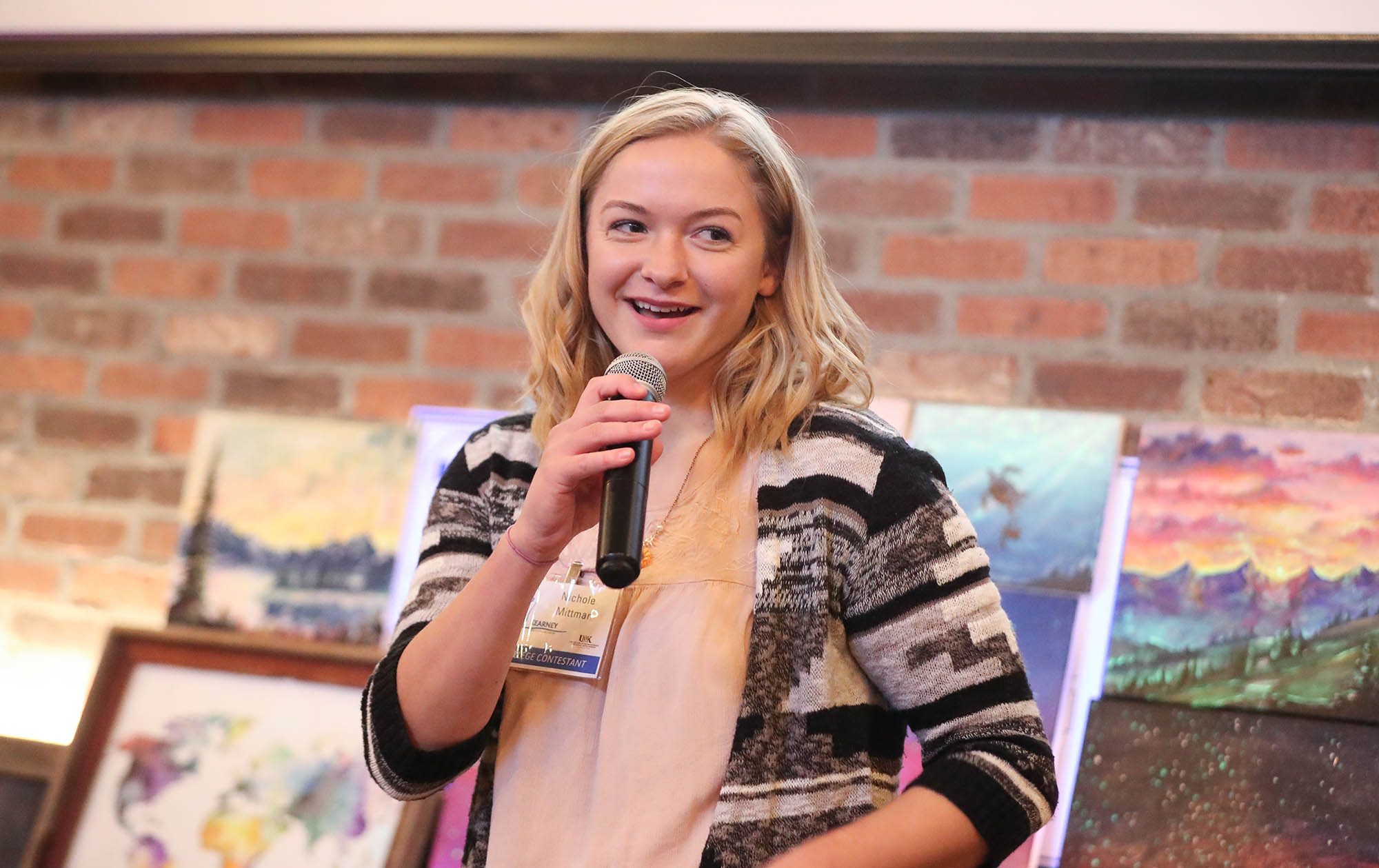 UNK sophomore Nicole Mittman talks about her glow-in-the-dark paintings during the Big Idea Kearney competition Wednesday evening at Cunningham's on the Lake. Mittman won the business contest's college division. (Photo by Corbey R. Dorsey, UNK Communications)