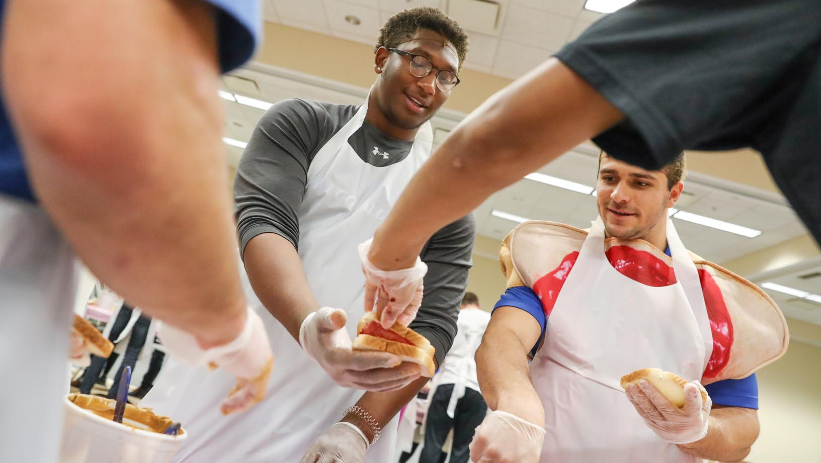 UNK football players Dakarai Monegain-Box, left, and Luke Quinn work with other student-athletes Tuesday during a peanut butter and jelly sandwich drive on campus. UNK Athletics partnered with Sodexo to make and distribute nearly 3,500 sandwiches. (Photos by Corbey R. Dorsey, UNK Communications)