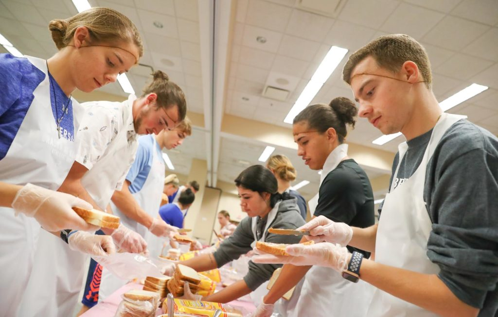 UNK student-athletes make peanut butter and jelly sandwiches Tuesday during a community service project on campus.