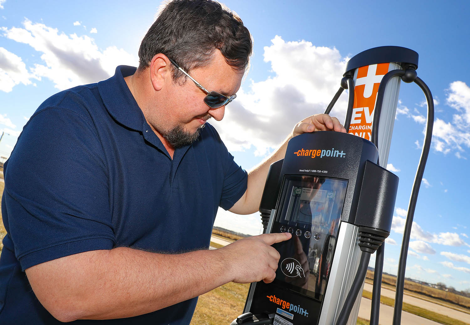 Consumer safety manager Marshall Barth demonstrates the electric vehicle charging station recently installed at the Nebraska Safety Center's driving range. The charging station is available for public use.
