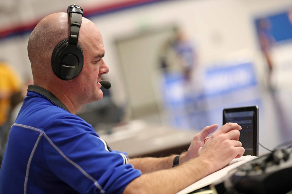 "KRVN play-by-play broadcaster Jayson Jorgensen calls Saturday's NCAA Division II title match in Denver. ""I appreciate this because I realize these moments, national championship settings like this, don't come around often,"" Jorgensen said. (Photo by Corbey R. Dorsey, UNK Communications)"
