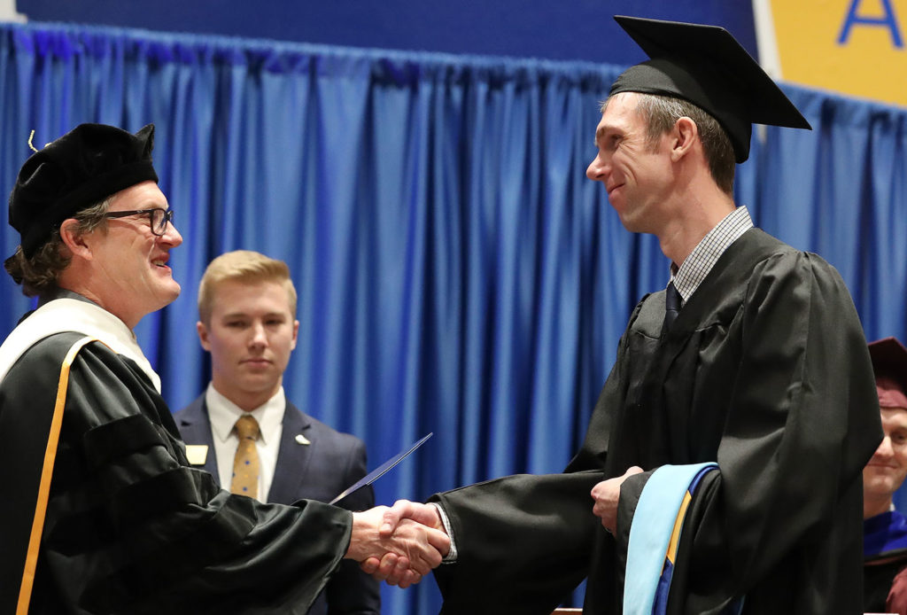 UNK Dean of Graduate Studies Mark Ellis, left, congratulates Brett Kluever during Friday's winter commencement at the Health and Sports Center. Kluever and his wife Sara both received Master of Education degrees in instructional technology.